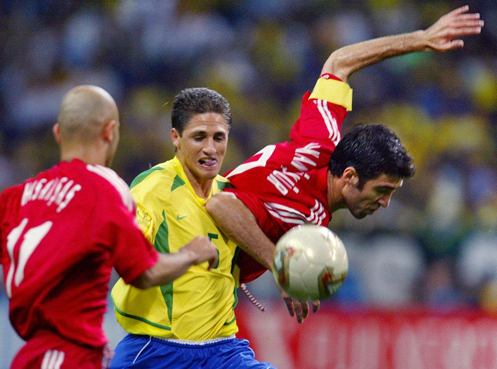 O zagueiro brasileiro Edmilson na disputa com atacante da Turquia Hasan Sas e com capitão Hakan Sukur durante o jogo das semifinais da Copa do Mundo da FIFA em 26 de junho de 2002.