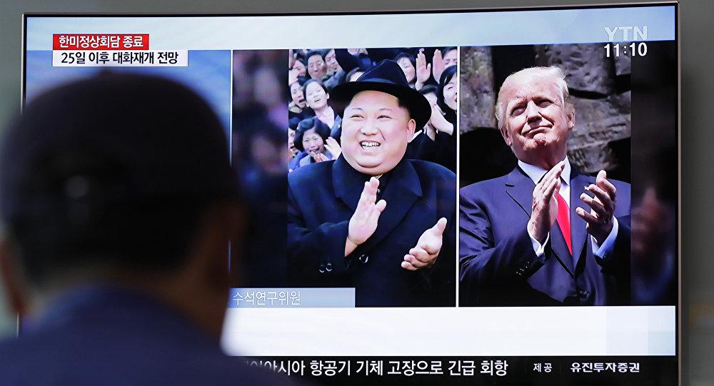 Um homem assiste um programa de TV mostrando o presidente dos EUA, Donald Trump, à direita, e o líder norte-coreano Kim Jong Un, à esquerda.