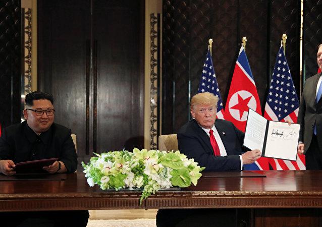 O presidente dos EUA, Donald Trump, mostra o documento assinado com o líder norte-coreano, Kim Jong-un