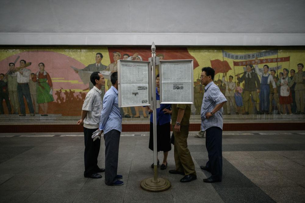 Cidadãos norte-coreanos leem as notícias em uma estação de metrô em Pyongyang, em meio à cúpula histórica entre Donald Trump e Kim Jong-un em Singapura, em 12 de junho de 2018
