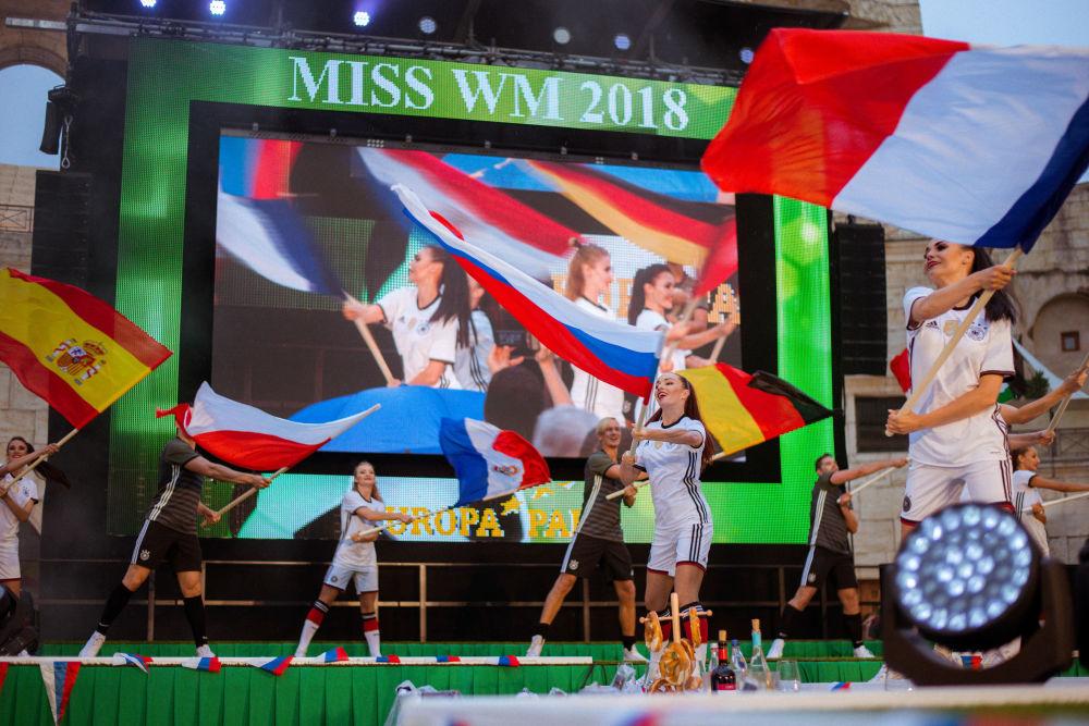 Participantes do concurso dançam com suas bandeiras nacionais no palco