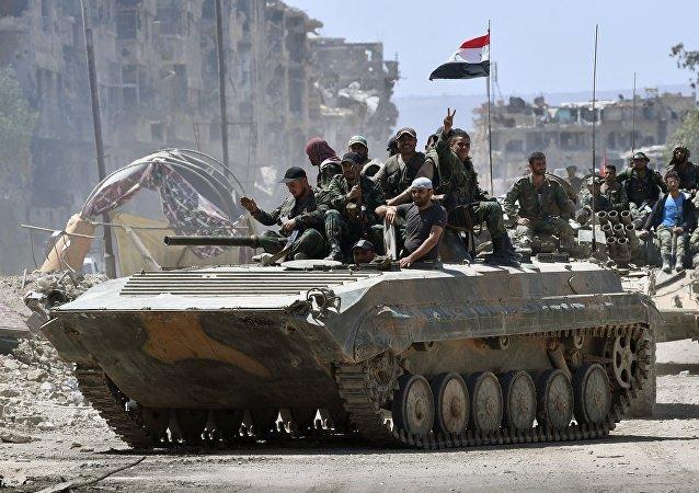 Soldados do Exército Sírio em um BMD-1 no campo de refugiados palestinos liberados de Yarmouk, ao sul de Damasco
