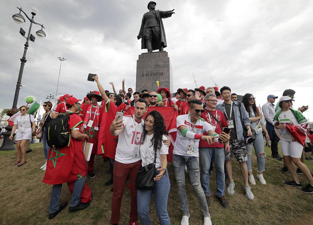 Torcedores de Irã e Marrocos tiram selfies na frente da estátua do líder soviético Sergei Kirov, em São Petersburgo.