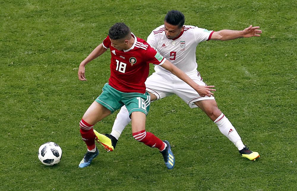 Amine Harit, do Marrocos, e Omid Ebrahimi, do Irã, dividem a bola.