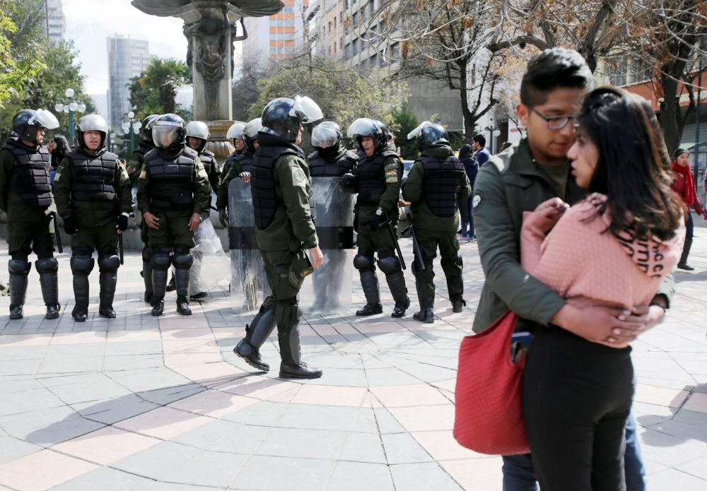 Um casal perto da polícia que está se preparando para os protestos estudantis na Universidade Pública de El Alto (UPEA), Bolívia
