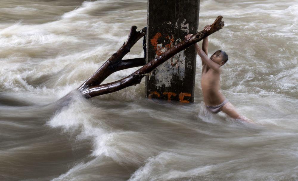 Uma criança segura um tronco debaixo de uma ponte parcialmente submersa depois das chuvas fortes em Manila, nas Filipinas