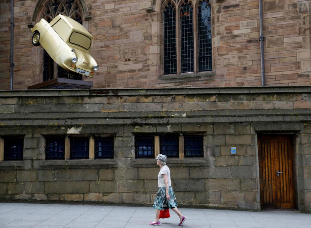 Uma mulher passa pela instalação 'Gold Lamé' do artista Tony Heaton, em Liverpool