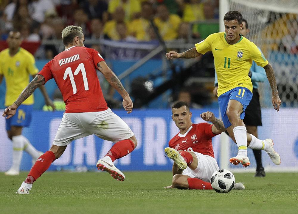 Philippe Coutinho, à esquerda, tenta vencer a marcação de Granit Xhaka, que desliza ao centro e do camisa 11 suíço, Behrami, à direita. O lance é parte do jogo entre Brasil e Suíça na estreia das seleções no grupo E durante a Copa do Mundo de 2018, na Rússia.