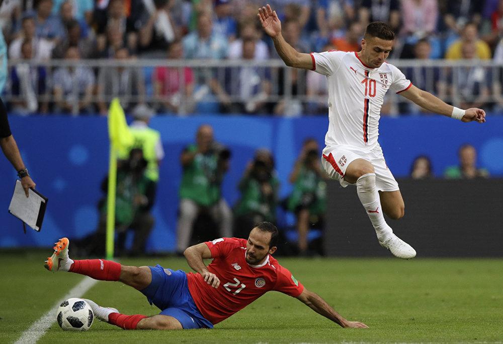 Jogador da Sérvia, Dusan Tadic, salta sobre o costa-riquenho Marcos Urena, que desliza sobre o gramado durante o jogo entre Sérvia e Costa Rica, na Copa do Mundo de 2018.