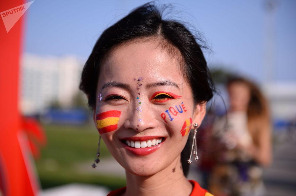 Torcedora da Espanha com nome do jogador da Seleção Gerard Piqué e bandeira nacional pintados no rosto.