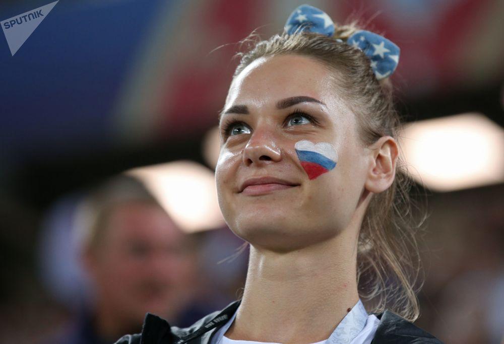 Torcedora com bandeira russa pintada no rosto vendo o jogo entre Croácia e Nigéria.