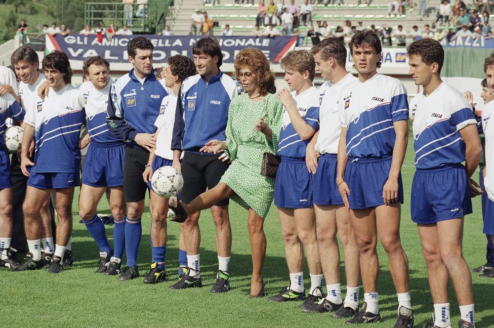 Atriz italiana Sophia Loren cercada por futebolistas durante a cerimônia de abertura do estádio de Marino, Itália, 1990