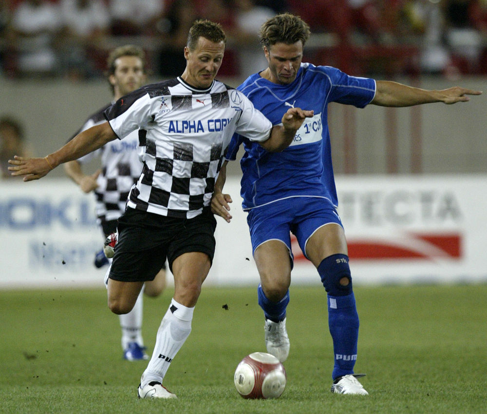 Automobilista Michael Schumacher do time Nazionale Piloti com seu adversário ator Sommer do time All Star Greece durante um jogo de beneficiência no estádio de Karaiskaki, Grécia, 2006