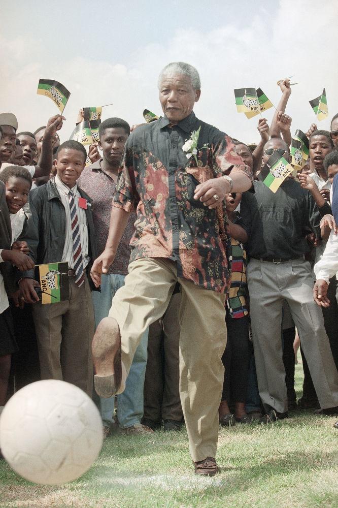 Presidente da África do Sul, Nelson Mandela, chutando bola em uma escola na África do Sul, 1994