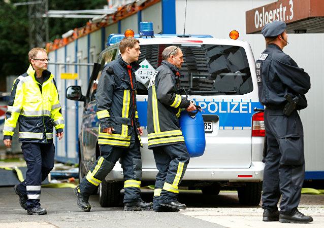 Um funcionário carrega um barril de plástico em frente ao apartamento de Sief Allah H., 29 anos, em Colônia, Alemanha, em 15 de junho de 2018. Ele é tunisiano e foi detido em 13 de junho de 2018, suspeito de planejar um ataque motivado por islamistas e a fabricação de uma arma biológica usando ricina