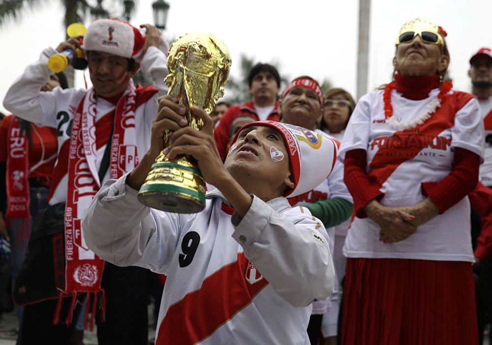 Torcedor peruano ergue réplica da taça da Copa do Mundo enquanto torce na cidade de Lima.