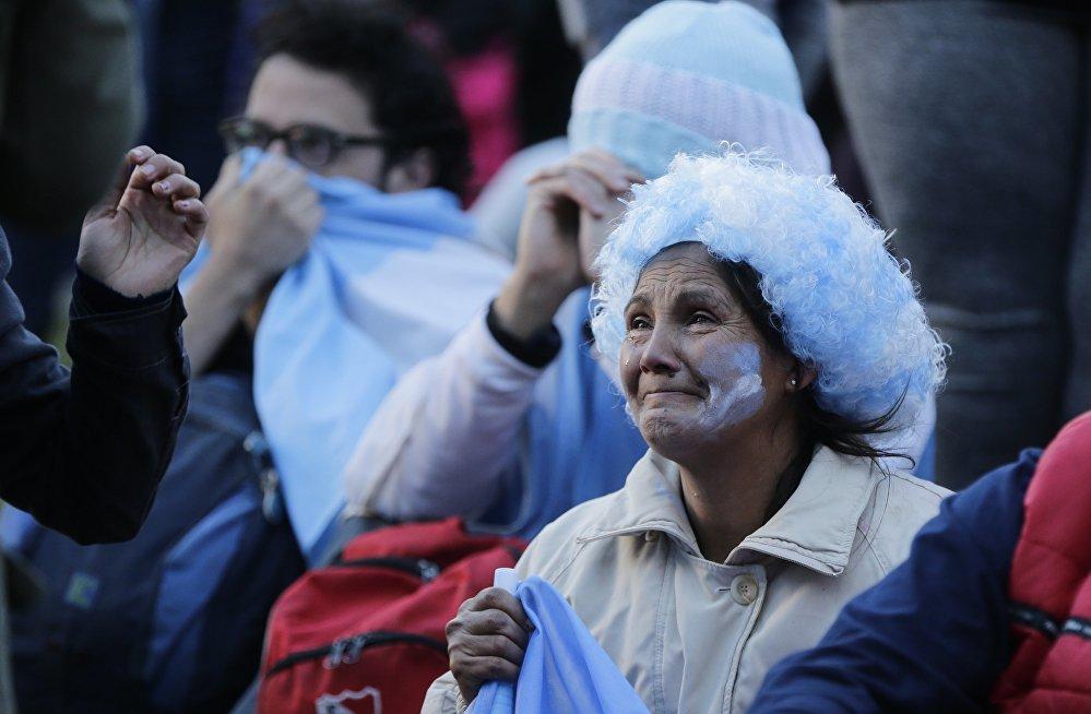 Torcedora argentina lamenta derrota da seleção de Messi contra a Croácia enquanto assiste ao jogo em Buenos Aires.