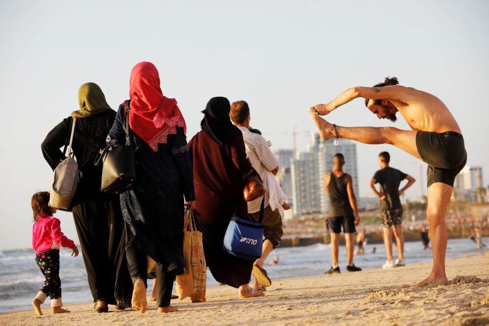 Pessoas curtindo a praia na costa do mar Mediterrâneo durante a celebração muçulmana de Eid al-Fitr, que marca o fim do jejum do Ramadã, Tel Aviv, Israel.