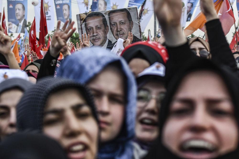 Apoiadores saudando o presidente turco e líder do Partido da Justiça e Desenvolvimento (AKP), Recep Tayyip Erdogan, durante um comício pré-eleitoral em Istanbul.