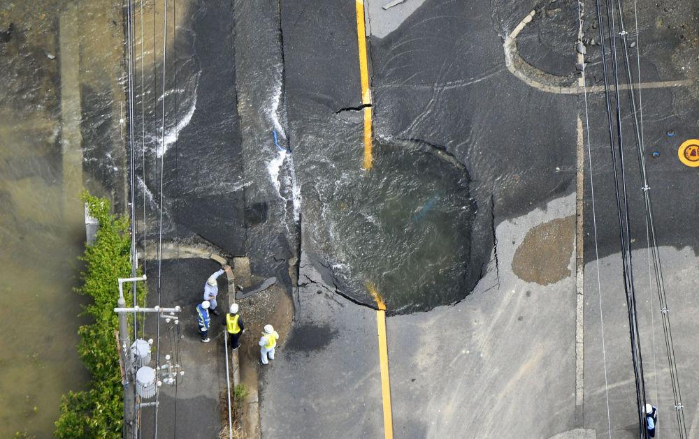 Água saindo de um buraco em uma estrada danificada por terremoto em Takatsuki, Japão.