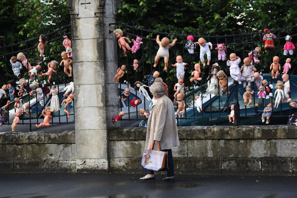 Bonecas penduradas na cerca de um hospital na França em protesto contra reduções de pessoal na maternidade.
