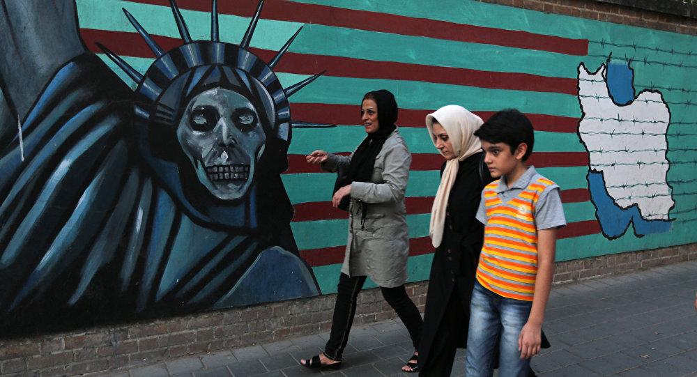 Uma família iraniana passa por pichações contrárias aos EUA na parede da antiga embaixada americana em Teerã.