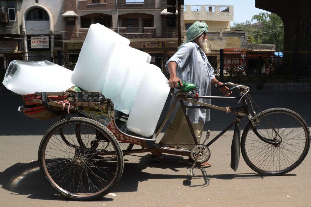 Morador de Amritsar (Índia) transporta gelo em 27 de maio de 2015, mais um dia de imenso calor.