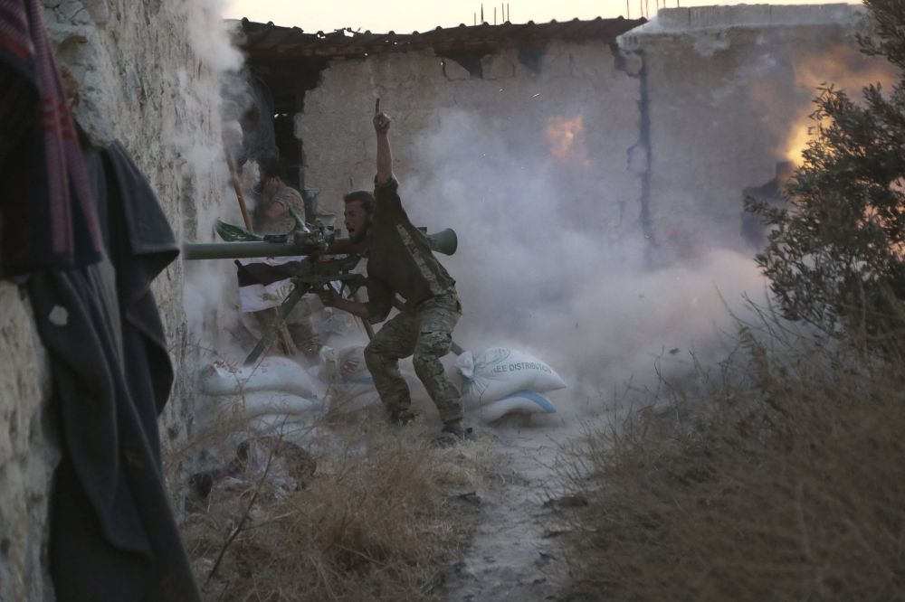 Rebelde sírio dispara contra as forças leais ao presidente da Síria, Bashar Assad, em 23 de maio de 2015.
