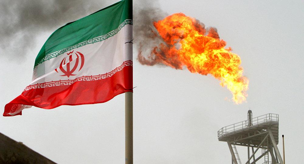 Uma tocha em uma plataforma de produção de petróleo nos campos de petróleo de Soroush. Ao lado, uma bandeira iraniana (foto de arquivo)