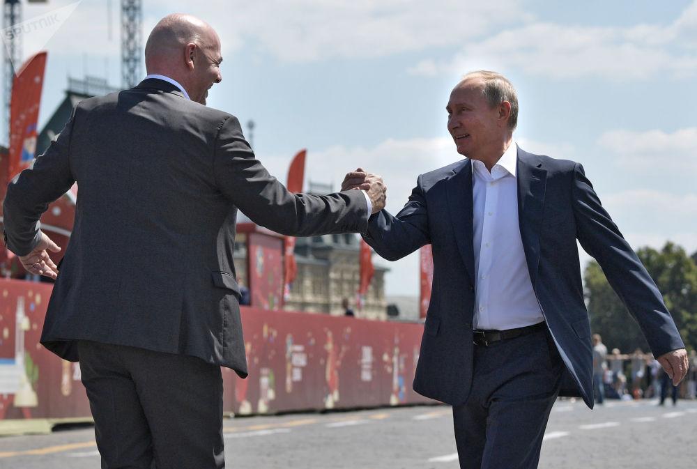 O Presidente da Rússia, Vladimir Putin, e o presidente da FIFA, Gianni Infantino, apertam mãos durante um passeio pelo parque de futebol instalado na Praça Vermelha, bem no centro de capital russa