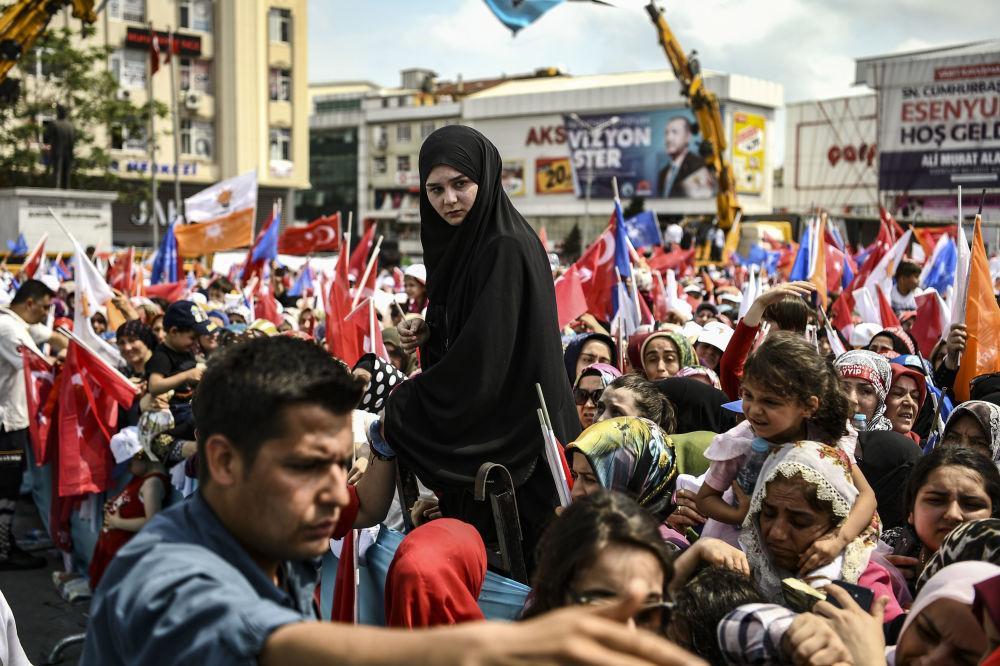 Pessoas assistem ao discurso do presidente da Turquia na véspera das eleições presidenciais em Istambul