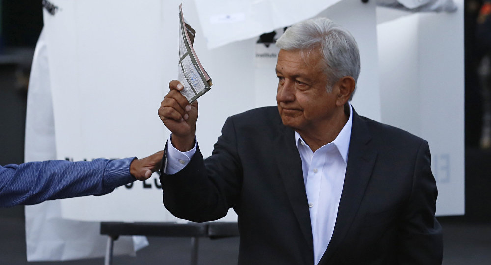 Presidential candidate Andres Manuel Lopez Obrador, of the MORENA party, shows his ballot to the press before casting it during general elections in Mexico City, Sunday, July 1, 2018. Sunday's elections for posts at every level of government are Mexico's largest ever and have become a referendum on corruption, graft and other tricks used to divert taxpayer money to officials' pockets and empty those of the country's poor