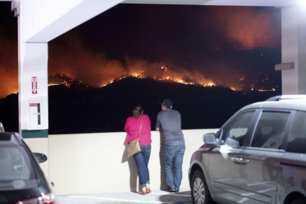 Pessoas olhando para incêndios florestais à noite, Califórnia