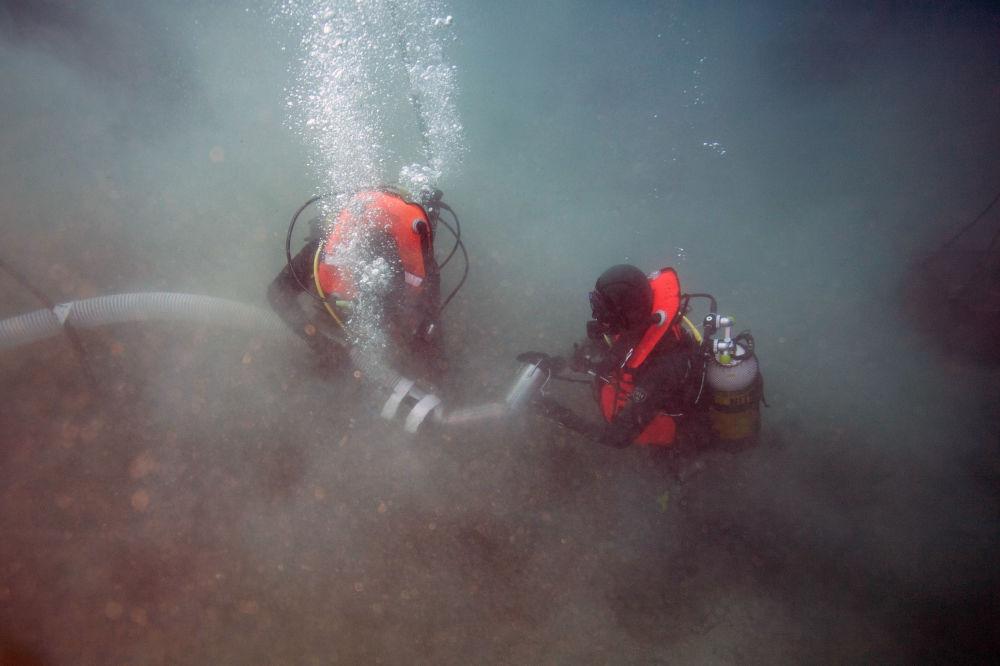 Mergulhadores militares franceses com bomba perto dos destroços do avião norte-americano P-47 Thunderbolt, perto da ilha de Córsega