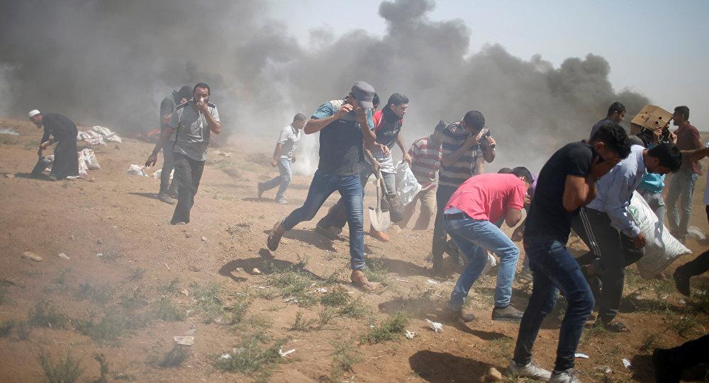 Manifestantes palestinos correm de gás lacrimogêneo disparado por tropas israelenses durante um protesto que marca o Dia de Al-Quds, (Dia de Jerusalém), na fronteira entre Israel e Gaza.