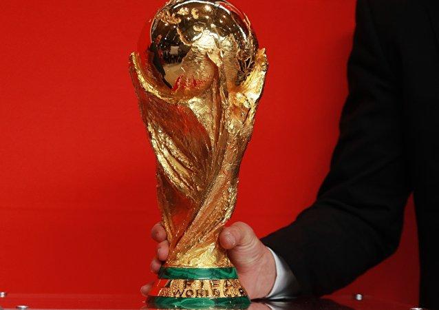 Lothar Matthaus segura a Taça da Copa do Mundo durante uma exposição do objeto no Aeroporto Internacional Sheremetyevo em Moscou, Rússia.