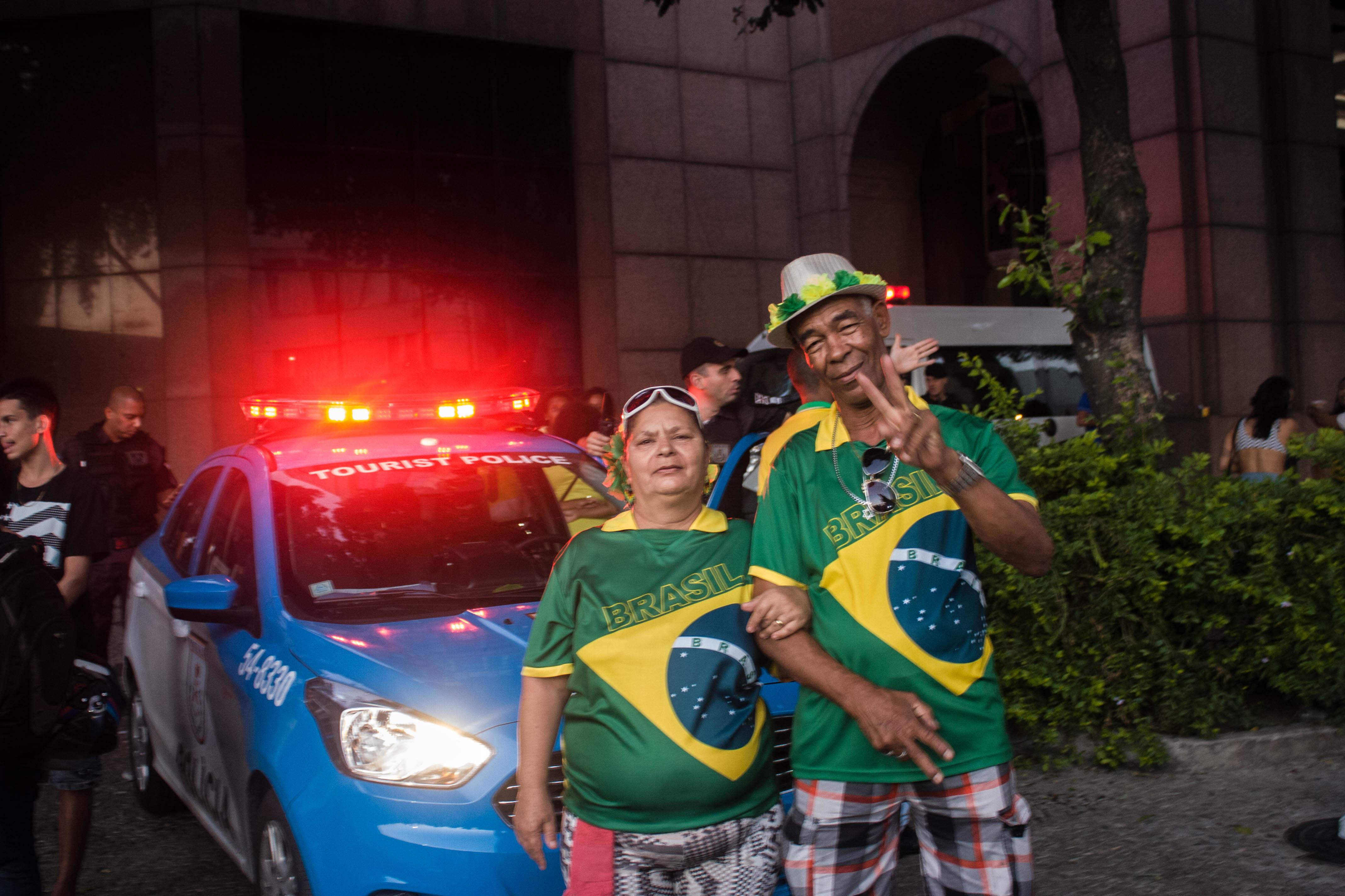 José Bispo de Oliveira posa ao lado da esposa em frente a uma viatura da Polícia Militar do Rio de Janeiro. Eles assistiram ao jogo do Brasil contra a Bélgica meio de uma multidão no Centro da cidade.