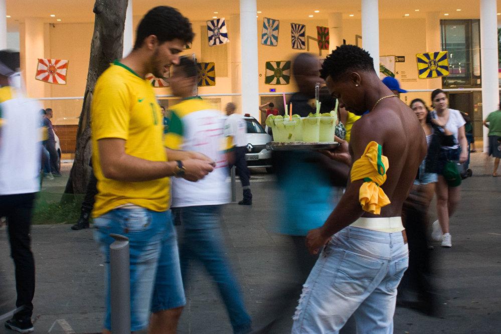 Torcedor compra caipirinha de ambulante durante transmissão do jogo entre Brasil e Bélgica na Praça Mauá, Rio de Janeiro. Centenas de ambulantes vendiam bebidas durante as transmissões.