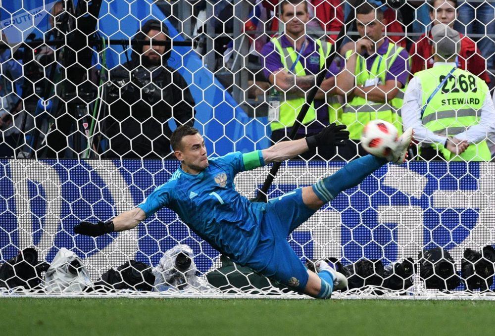 Goleiro da Seleção Russa, Igor Akinfeev, rebatendo a bola com o pé no jogo das oitavas entre as seleções da Espanha e da Rússia