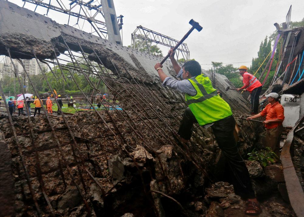 Funcionários do serviço de resgate e da ferrovia trabalhando no local da queda de uma ponte sobre os trilhos da via devido a fortes chuvas em Bombaim, Índia