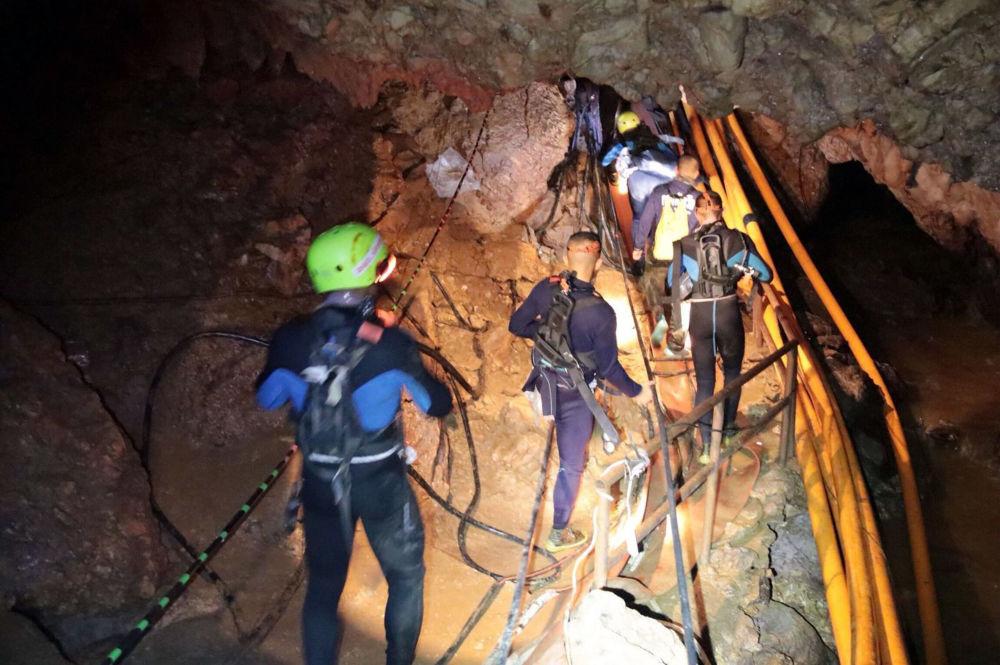 Salvadores tailandeses dentro da caverna inundada durante a operação de resgate para libertar os meninos bloqueados
