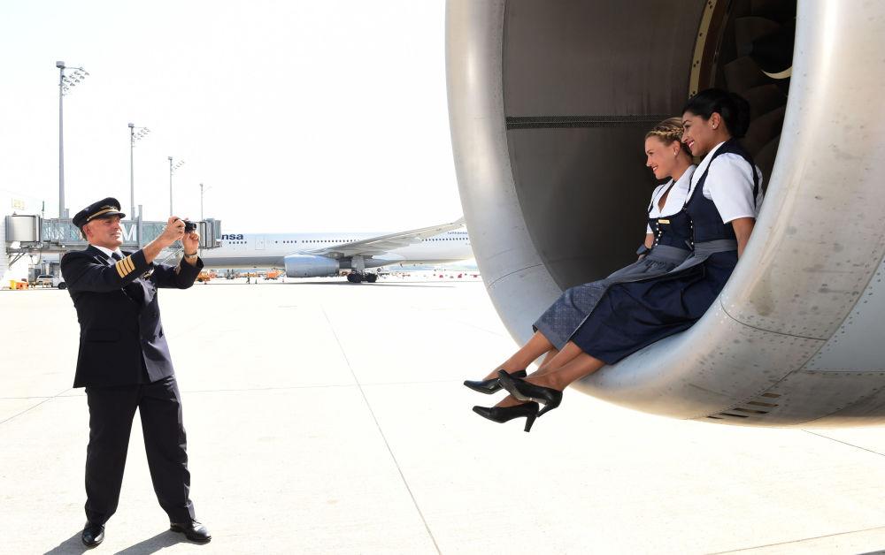 Aeromoças em roupas tradicionais da Bavária posando no aeroporto de Munique