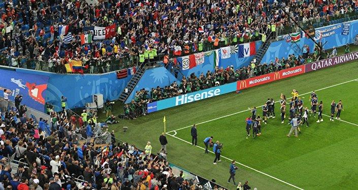 Jogadores franceses vencem a Bélgica e comemoram com a torcida no estádio de São Petersburgo.