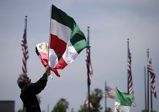 Um manifestante anônimo agitando bandeiras iranianas em Los Angeles, EUA (foto de arquivo)