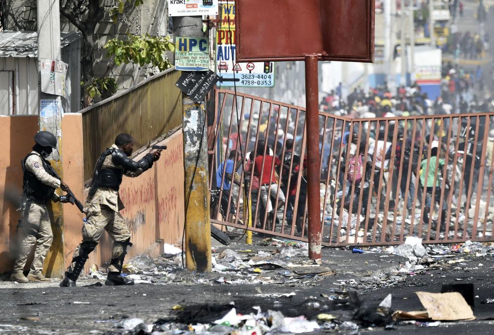 Policial haitiano aponta pistola à multidão durante os protestos contra o aumento dos preços dos combustíveis, nos arredores de Porto Príncipe