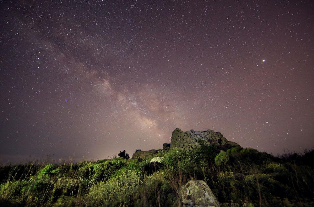 Via Láctea em cima da torre-fortaleza, Nurague, na ilha da Sardenha, na Itália