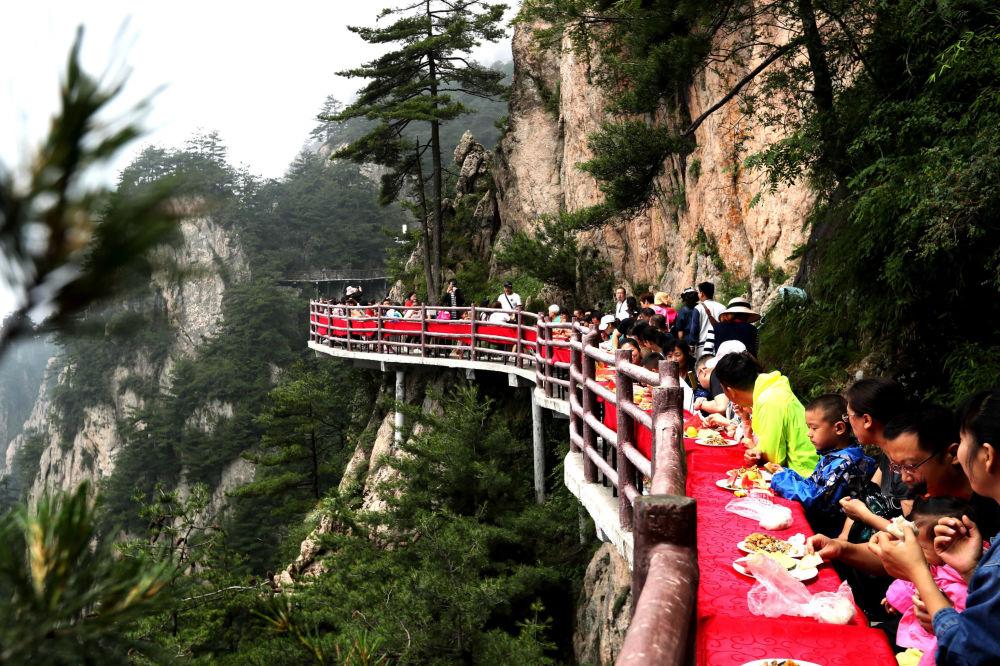 Turistas durante um banquete organizado à beira de uma falésia, na China
