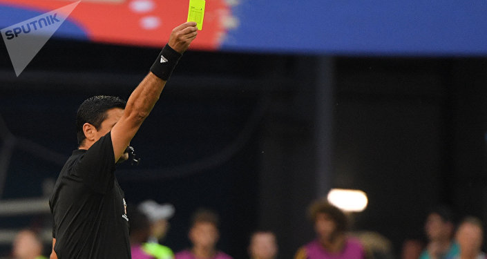O juiz Alireza Faghani mostra o cartão amarelo para o zagueiro John Stones depois de um puxão na camisa de Eden Hazard, matando o contra-ataque belga.