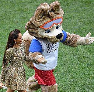 A soprano russa Aida Garifullina caminha com o mascote oficial da Copa do Mundo de 2018, o lobo Zabivaka durante a cerimônia de encerramento da Copa do Mundo.