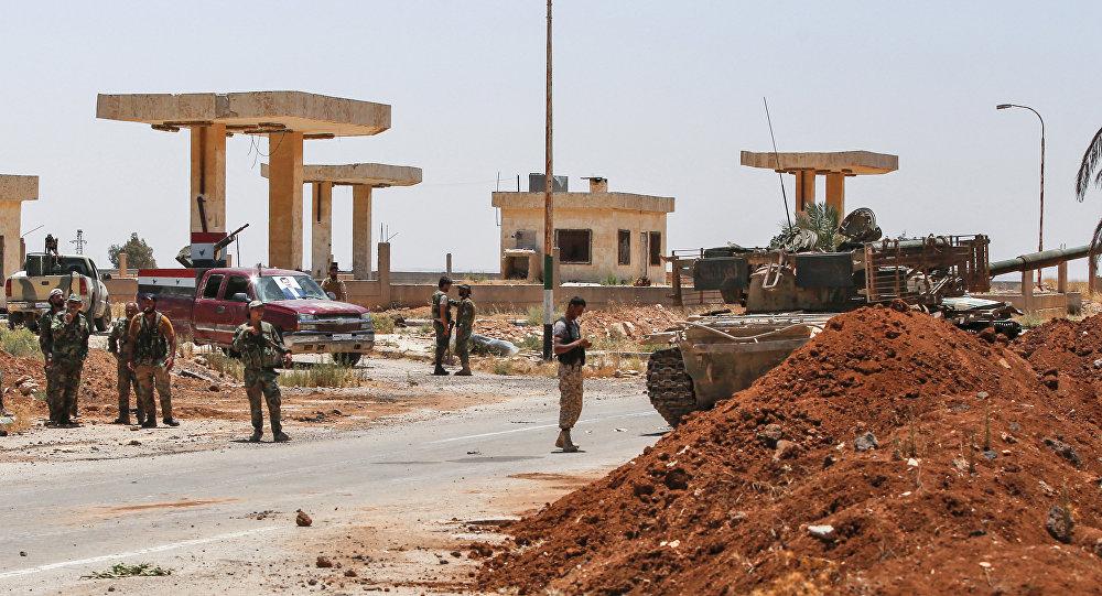 Soldados do governo sírio estão ao lado de um tanque e de caminhonetes armadas na fronteira de Nassib com a Jordânia, na província de Daraa.